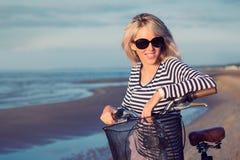 Retrato de la mujer de moda joven con la bicicleta en la playa Imagenes de archivo