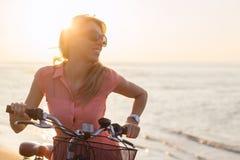 Retrato de la mujer de moda joven con la bicicleta en la playa Foto de archivo