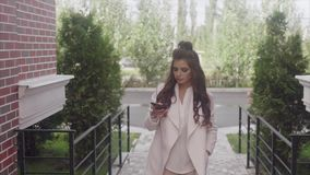 Retrato de la mujer de negocios acertada joven que usa su smartphone al aire libre metrajes