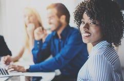 Retrato de la mujer de negocios afroamericana bonita con la sonrisa afro en la cámara Equipo de Coworking en la reunión de reflex imagen de archivo libre de regalías