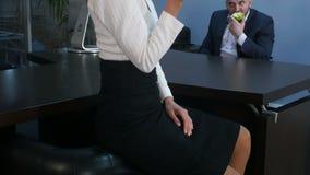 Retrato de la mujer de negocios agradable y bastante joven que sonríe y que sostiene una manzana verde almacen de metraje de vídeo