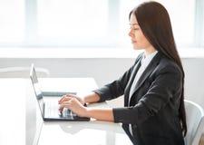 Retrato de la mujer de negocios bonita con el ordenador portátil en el offic Fotografía de archivo libre de regalías