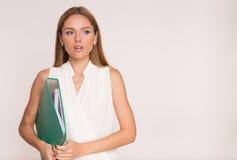 Retrato de la mujer de negocios con la carpeta verde, aislado en blanco Imagen de archivo
