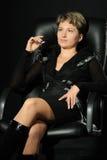 Retrato de la mujer de negocios en un armcha de cuero Imagen de archivo libre de regalías