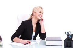 Retrato de la mujer de negocios feliz que se sienta en su escritorio Foto de archivo libre de regalías