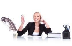 Retrato de la mujer de negocios feliz que se sienta en su escritorio Imagen de archivo libre de regalías