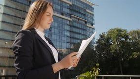 Retrato de la mujer de negocios hermosa joven que se sostiene y papeles de la ojeada al aire libre almacen de metraje de vídeo
