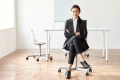 Retrato de la mujer de negocios hermosa que se sienta en silla imagen de archivo