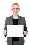 Retrato de la mujer de negocios joven alegre que lleva a cabo un espacio en blanco blanco Foto de archivo