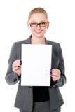 Retrato de la mujer de negocios joven alegre que lleva a cabo un espacio en blanco blanco Imagen de archivo libre de regalías