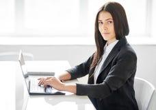 Retrato de la mujer de negocios joven con el ordenador portátil en el offic Fotos de archivo