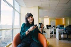Retrato de la mujer de negocios joven positiva que se sienta en la oficina moderna que sonríe y que mira el teléfono Imagen de archivo
