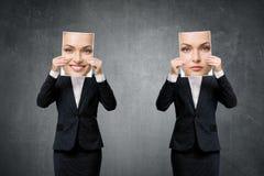 Retrato de la mujer de negocios joven que oculta su humor bajo máscaras Foto de archivo