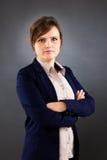 Retrato de la mujer de negocios joven que se coloca con los brazos cruzados Fotografía de archivo
