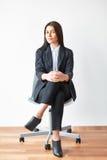 Retrato de la mujer de negocios joven que se sienta en silla fotografía de archivo libre de regalías