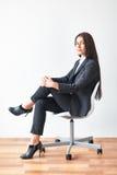 Retrato de la mujer de negocios joven que se sienta en silla foto de archivo
