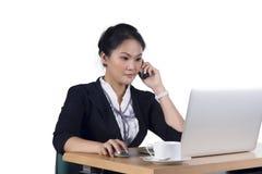 Retrato de la mujer de negocios que habla en el teléfono móvil mientras que usa Fotografía de archivo libre de regalías