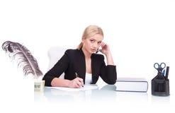 Retrato de la mujer de negocios seria que se sienta en su escritorio Foto de archivo