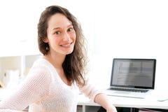 Retrato de la mujer de negocios sonriente joven en el trabajo Fotografía de archivo libre de regalías