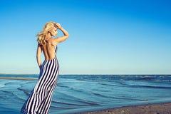 Retrato de la mujer de pelo largo rubia encantadora en vestido rayado blanco y negro largo con caminar trasero desnudo a lo largo Foto de archivo