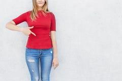 Retrato de la mujer de pelo rubio que señala con su dedo índice en el espacio de la copia en su suéter rojo que demuestra algo in Fotos de archivo