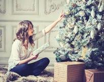 Retrato de la mujer del Año Nuevo cerca del árbol de navidad con las cajas de regalo Foto de archivo libre de regalías