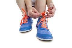 Retrato de la mujer del atleta que ata sus zapatillas deportivas Imagen de archivo libre de regalías