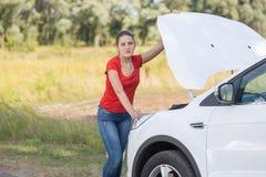 Retrato de la mujer del trastorno que se coloca en el coche quebrado en el borde de la carretera Foto de archivo