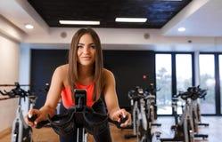 Retrato de la mujer delgada joven en entrenamiento del sportwear en la bicicleta est?tica en gimnasio Concepto de la forma de vid imagen de archivo libre de regalías