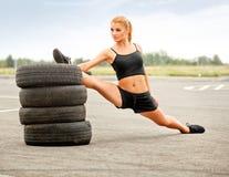 Retrato de la mujer deportiva joven que hace estirando ejercicio. Athlet Imagen de archivo