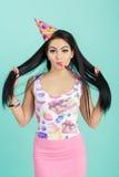 Retrato de la mujer divertida en sombrero del cumpleaños y camisa rosada en fondo azul Celebración y partido Padre y niño que jue Fotos de archivo
