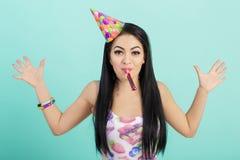 Retrato de la mujer divertida en sombrero del cumpleaños y camisa rosada en fondo azul Celebración y partido Padre y niño que jue Imagen de archivo libre de regalías