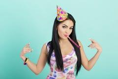 Retrato de la mujer divertida en sombrero del cumpleaños y camisa rosada en fondo azul Celebración y partido Padre y niño que jue Foto de archivo