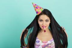 Retrato de la mujer divertida en sombrero del cumpleaños y camisa rosada en fondo azul Celebración y partido Padre y niño que jue Fotos de archivo libres de regalías