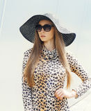 Retrato de la mujer elegante hermosa que lleva un vestido del leopardo, un sombrero de paja y gafas de sol fotografía de archivo libre de regalías