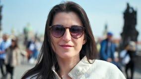 Retrato de la mujer elegante hermosa sonriente en la presentación de las gafas de sol rodeada por la muchedumbre de gente almacen de video