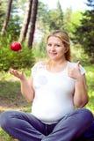 Retrato de la mujer embarazada al aire libre, nuevo concepto de la vida, relajándose en parque con la manzana Imagen de archivo libre de regalías