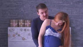 Retrato de la mujer embarazada del pelirrojo alegre y su del marido que se colocan cerca de uno a Manos de la mamá y del papá en  metrajes