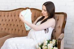 Retrato de la mujer embarazada hermosa joven feliz que se sienta en vint Fotografía de archivo