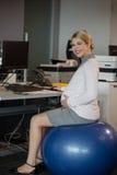 Retrato de la mujer embarazada que se sienta en bola de la aptitud mientras que trabaja en el escritorio Fotografía de archivo