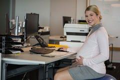 Retrato de la mujer embarazada que se sienta en el escritorio Foto de archivo