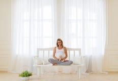 Retrato de la mujer embarazada que se sienta en una actitud del loto Fotografía de archivo