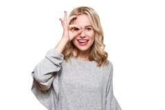 Retrato de la mujer emocionada hermosa en ropa informal que sonríe y que muestra la muestra aceptable en la cámara aislada sobre  imagen de archivo
