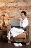 Retrato de la mujer en albornoz con la computadora portátil Fotografía de archivo