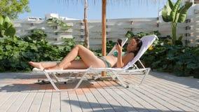 Retrato de la mujer en bikini encendido en Sunbed en casa en terraza almacen de video
