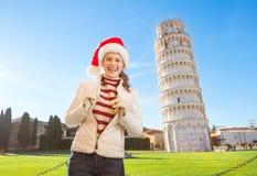 Retrato de la mujer en el sombrero de Papá Noel delante del viaje que se inclina de Pisa Foto de archivo