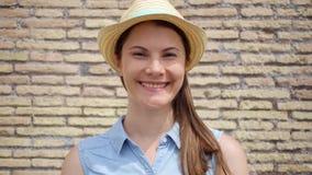 Retrato de la mujer en el sombrero que se opone a la pared de ladrillo roja Viajero femenino que sonríe en la cámara lenta almacen de metraje de vídeo