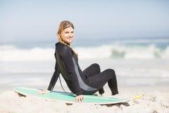 Retrato de la mujer en el wetsuit que se sienta con la tabla hawaiana en la playa Imagenes de archivo