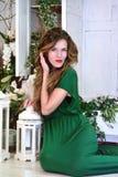 Retrato de la mujer en la sentada larga del vestido de noche del verde de la moda de la belleza Imagen de archivo libre de regalías
