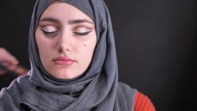 Retrato de la mujer en los vidrios que dibujan la flecha negra usando el cepillo fino para la mujer musulmán joven en hijab en fo almacen de video